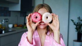 Lächelndes Mädchen, das seine Augen mit glasig-glänzenden Schaumgummiringen bedeckt Hübsche Frau, die Spaß hat stock video