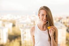 Lächelndes Mädchen, das von der Orange trinkt Stockfotos