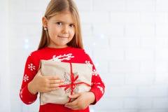 Lächelndes Mädchen, das Weihnachtsgeschenk hält lizenzfreie stockfotos