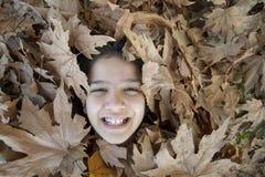 Lächelndes Mädchen in den Blättern Lizenzfreies Stockfoto