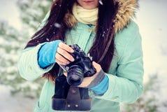 Lächelndes Mädchen des Brunette fotografierte auf einer alten Weinlesekamera im Winterwald lizenzfreies stockbild