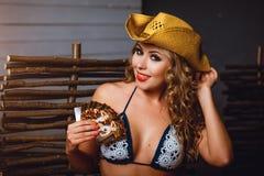 Lächelndes Mädchen in einem Bikini, in roten Lippen und in einem Cowboyhut Stockfotografie