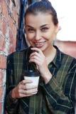 Lächelndes Mädchen in einem Plaid grünen das Hemd, das Wegwerfkaffeetasse steht Stockbilder