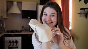 Lächelndes Mädchen in einem Schutzblech in der Küche zerreißt rohen Teig mit ihren Händen Nettes Mädchenlachen und herum täuschen stock video footage
