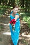 Lächelndes Mädchen gibt einen Blumenstrauß von roten Rosen Stockbilder