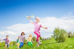 Lächelndes Mädchen hält Flugzeugspielzeug mit Kinderdem laufen Lizenzfreies Stockfoto