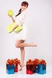 Lächelndes Mädchen hält Kästen mit Geschenken an und steht auf einem Fahrwerkbein Stockfotos