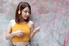 Lächelndes Mädchen in hörender Musik der gelben Sommerkleidung mit Kopfhörern und Handy auf hellem Hintergrund mit Kopienraum jun lizenzfreie stockfotografie