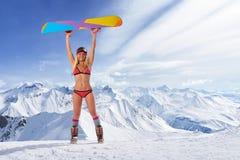 Lächelndes Mädchen im Bikini, der Snowboard über Kopf hält Lizenzfreies Stockfoto