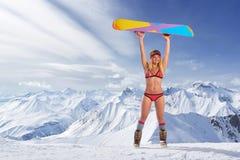 Lächelndes Mädchen im Bikini, der Snowboard über Kopf hält Stockbild