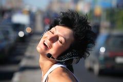 Lächelndes Mädchen im Kopfhörer stellte auf Datenbahnmitte ein Stockfotografie