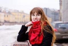 Lächelndes Mädchen im roten Schal Stockbilder