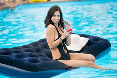 Lächelndes Mädchen im schwarzen Bikini, der ein Cocktail sitzt auf Matratze im Swimmingpool auf einem unscharfen Hintergrund des  Lizenzfreies Stockfoto