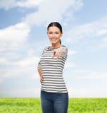Lächelndes Mädchen im zufälligen clother zeigend auf Sie Lizenzfreie Stockfotos