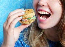 Lächelndes Mädchen isst Plätzchen Lizenzfreies Stockfoto