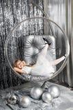 Lächelndes Mädchen liegt in einem transparenten Ball mit silbernen Weihnachtsbällen lizenzfreie stockfotografie