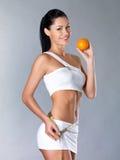 Lächelndes Mädchen misst Abbildung mit einer Orange Stockfotos