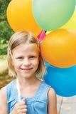 Lächelndes Mädchen mit Ballonen auf der Straße Lizenzfreie Stockbilder