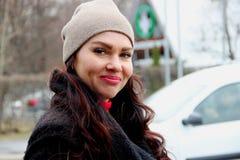 lächelndes Mädchen mit blauen Augen auf dem Hintergrund der Stadt und des Autos lizenzfreie stockfotografie