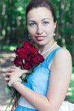 Lächelndes Mädchen mit Blumenstrauß von roten Rosen Lizenzfreie Stockfotos