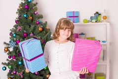 Lächelndes Mädchen mit, das den Geschenken sitzen nahe Weihnachtsbaum ist Stockbilder