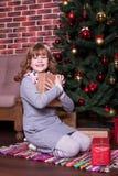 Lächelndes Mädchen mit, das den Geschenken sitzen nahe Weihnachtsbaum ist Lizenzfreies Stockfoto