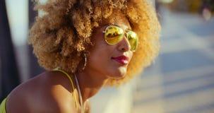 Lächelndes Mädchen mit dem Afro, der auf Promenade stillsteht stock footage