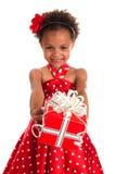 Lächelndes Mädchen mit dem Lockenhaar geben eine Geschenkbox in den Händen Guten Rutsch ins Neue Jahr- und Weihnachtsfeiertage Stockbilder
