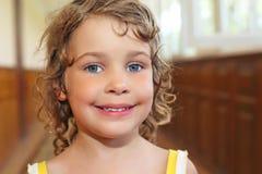 Lächelndes Mädchen mit dem lockigen Haar im Flur Stockbilder