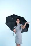 Lächelndes Mädchen mit dem Regenschirm, der für Regen cheking ist Stockfotos