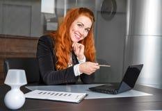 Lächelndes Mädchen mit dem roten Haar stellt auf dem Computer dar Stockfotos