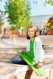 Lächelndes Mädchen mit dem Skateboard, das auf Spielplatz sitzt Stockfotos