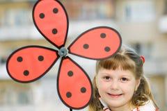 Lächelndes Mädchen mit farbigem Windmühlenspielzeug Stockfotos