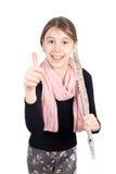 Lächelndes Mädchen mit Flöte auf ihrer Schulter, die den Daumen oben lokalisiert auf Weiß zeigt Lizenzfreies Stockbild