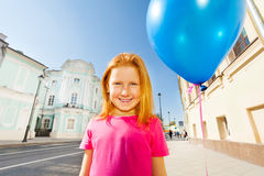 Lächelndes Mädchen mit Fliegenballon steht auf Straße lizenzfreie stockfotografie