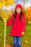 Lächelndes Mädchen mit gelber Rührstange steht im Park lizenzfreie stockbilder