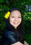 Lächelndes Mädchen mit Löwenzahnblume im Haar Lizenzfreie Stockbilder