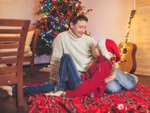 Lächelndes Mädchen mit Vati nahe Weihnachtsbaum zu Hause Lizenzfreie Stockfotografie