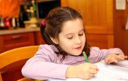 Lächelndes Mädchen schreibt auf ihr Notizbuch Stockbild