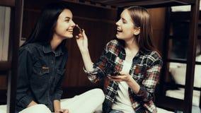 Lächelndes Mädchen sitzen auf Bett- und Farbenfreundin stockbilder