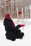 Lächelndes Mädchen sitzt auf Schnee und betrachtet hängenden Apfel Stockfotos