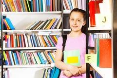 Lächelndes Mädchen steht nahes Bücherregal mit Lehrbuch lizenzfreie stockbilder