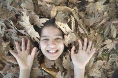 Lächelndes Mädchen stellen und Hände in den Blättern gegenüber Lizenzfreies Stockfoto