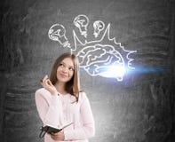 Lächelndes Mädchen und Gehirn mit Glühlampen Stockfotografie