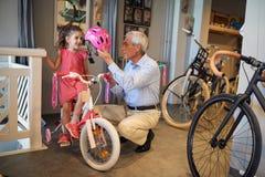 Lächelndes Mädchen und ihr großväterliches Kaufenfahrrad und -sturzhelme im Fahrradgeschäft lizenzfreies stockfoto