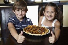 Lächelndes Mädchen und Junge mit Pizza Lizenzfreie Stockfotos