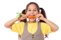 Lächelndes Mädchen, welches die Karotte beißt Lizenzfreie Stockfotografie