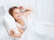 Lächelndes Mädchenkind, das zu Hause im Bett aufwacht Stockfotografie