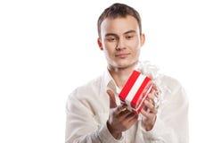 Lächelndes Mannholdinggeschenk getrennt auf Weiß stockfotografie