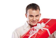 Lächelndes Mannholdinggeschenk getrennt auf Weiß lizenzfreies stockfoto